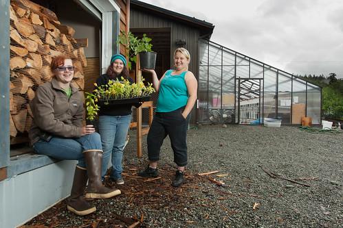Three high school girls show off a crop