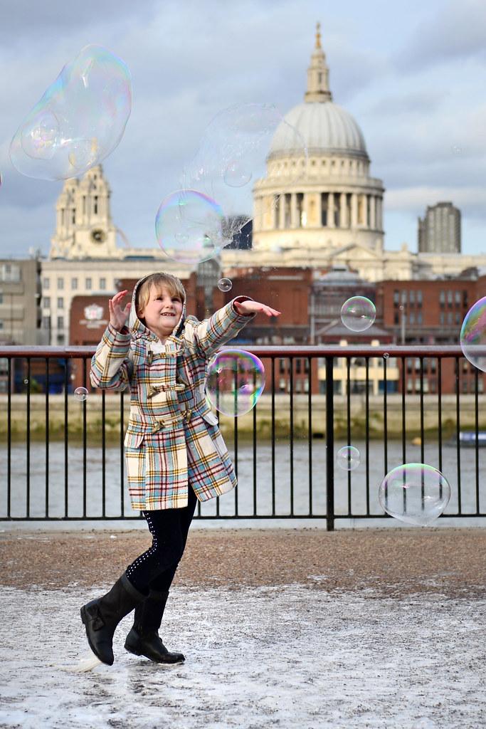 Niña jungando con pompas de jabón frente al paseo del Tate Museum de Londres
