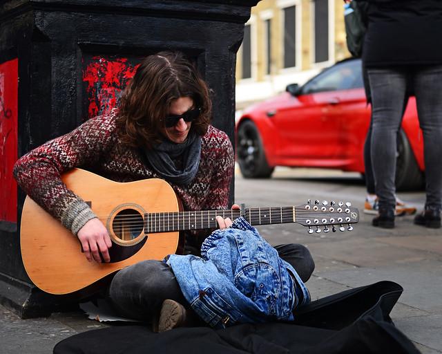 Guitarrista tocando su música en una acera de la calle de Camden Town