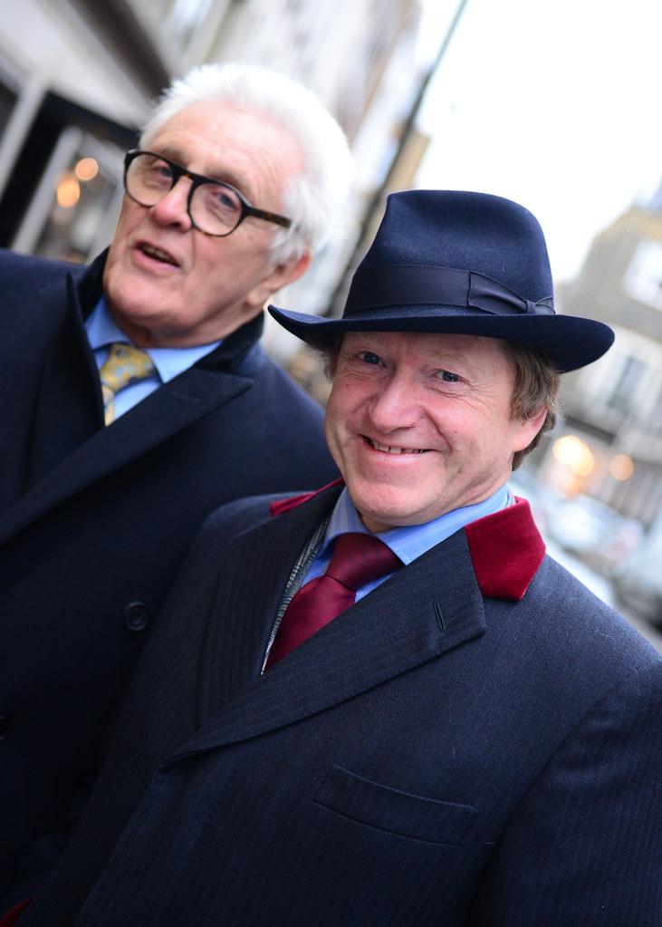 Dos caballeros saliendo de una tienda en la calle de los sastres de Londres
