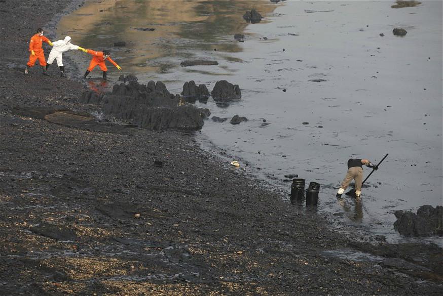 2010年,中國大連新港輸油管爆炸,漏油污染周遭海域,工作人員在海灣處清理油污。圖片來源:Greenpeace