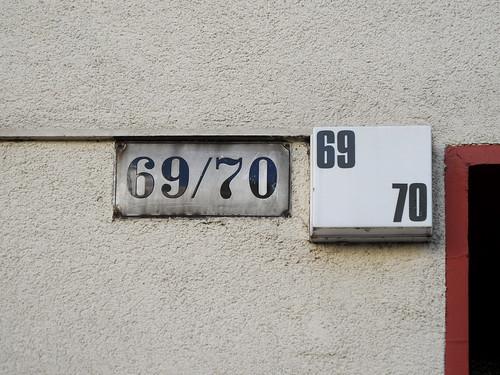 Ein altes Hausnummernschild aus Email neben einer modernen beleuchteten Hausnummer
