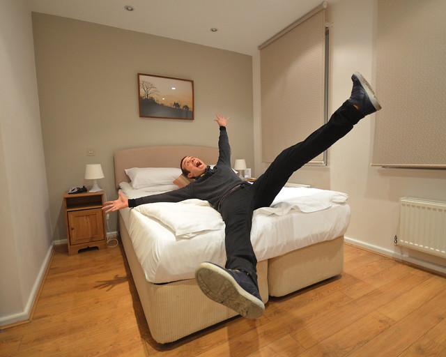 Con las piernas abiertas tirado en la cama de uno de los hoteles de Londres