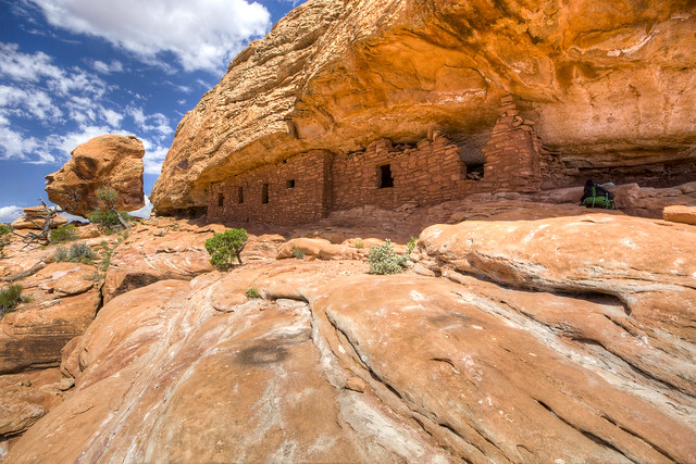 Image shows red sandstone cliff dwellings in pristine condition, tucked under an overhang. A large sandstone boulder balances precariously at the edge of the cliff in the distance.