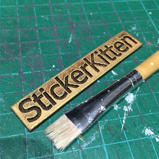 Dry brushing technique on MDF wooden logo using gold acrylic paint and decoupage bristle brush