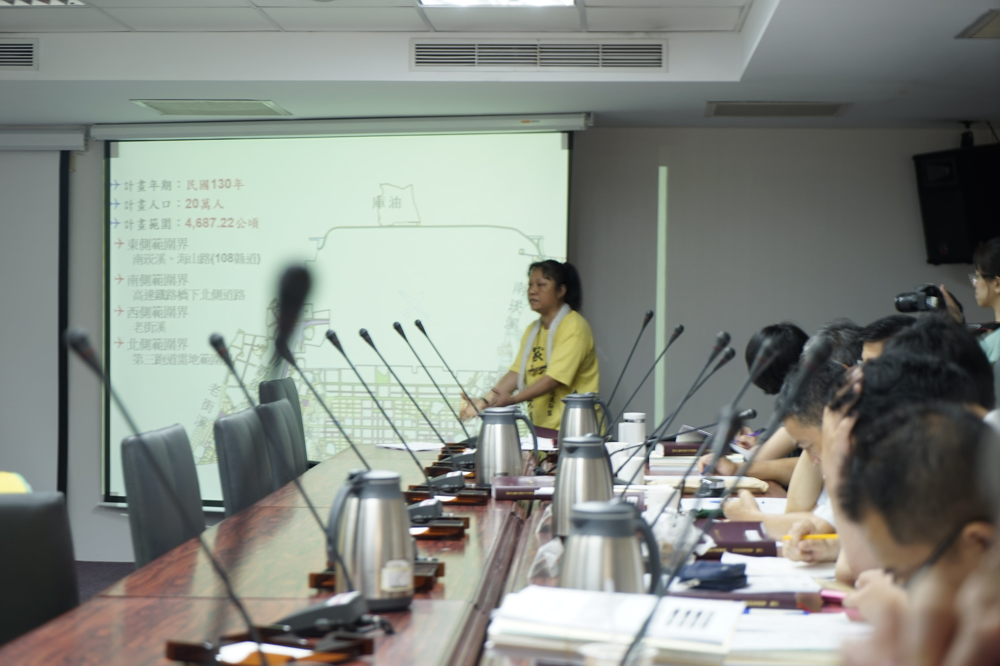航空城自救會成員在都委會中比劃著住家位置,反對政府大規模徵收。(攝影:張宗坤)