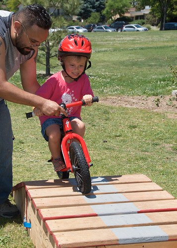 A man helping a boy ride his bike