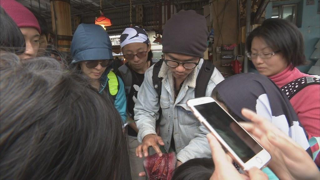 921-1-10 在地文史工作者廖大瑋,經常帶著外地來的遊客,走訪魚市場,為他們導覽。