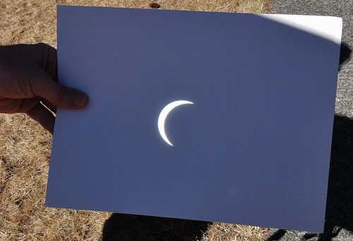 Image shows a hand holding a sheet of white paper. Most of it is in shadow. The sun is reflected as a brilliant white crescent: it's nearly completely eclipsed.