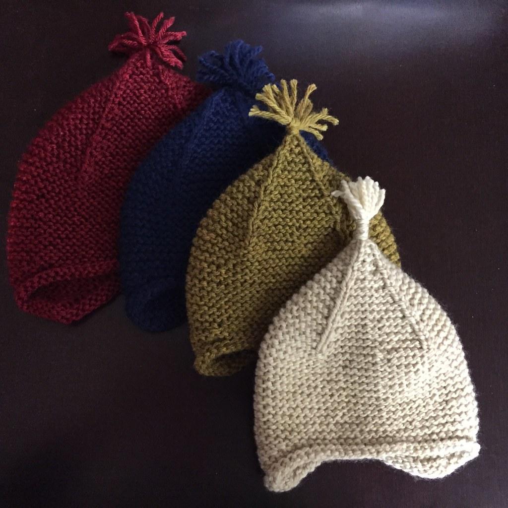 a little stack of newborn sized garter ear flap hats