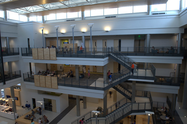 A photo shows the three stories of the Mell Classroom Building, including natural light coming in from the ceiling and the staircase to the right.