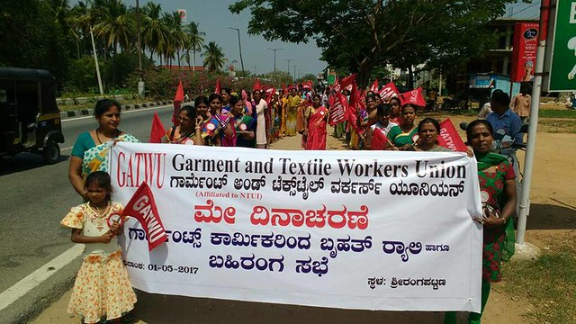 Two women leading a march of garment workers represented by Bangalore-based garment sector union GATWU, they are holding a banner bearing their name and text in Kannada.