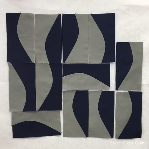 twelve navy and grey gentle improv curve units on design wall