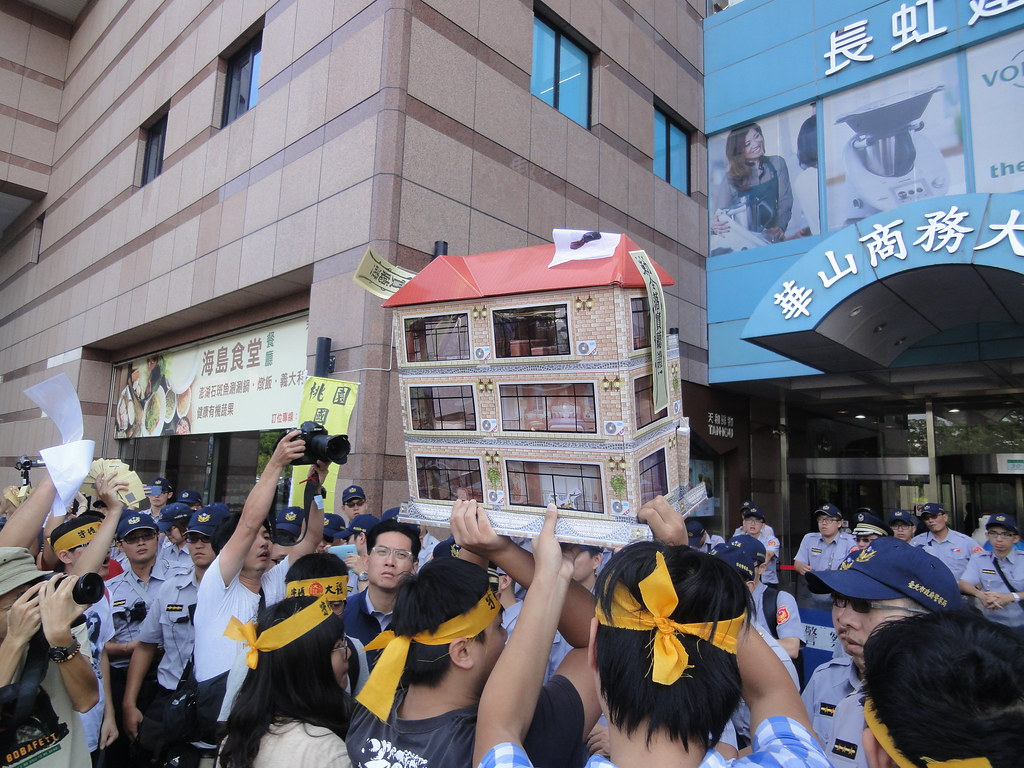 抗爭居民作勢將象徵家園的房屋抬進民進黨總部,和警方發生短暫推擠衝突。(攝影:張智琦)