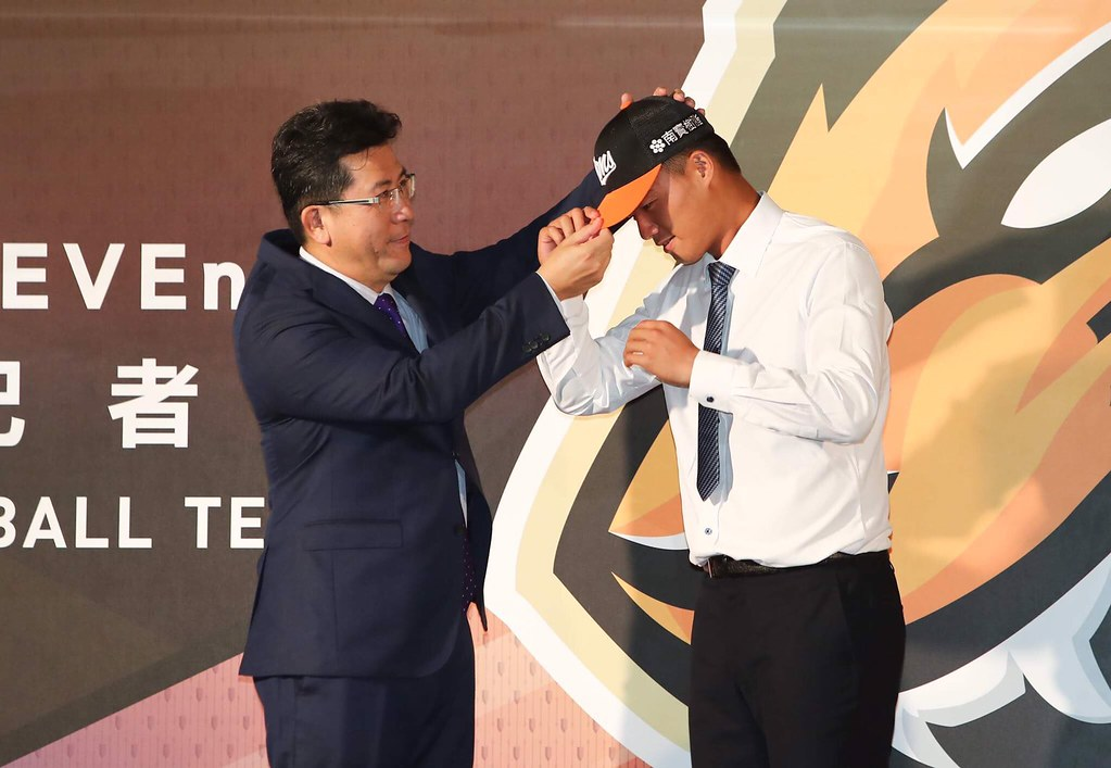 統一董事凃忠正(左)為施子謙戴上統一獅球帽。(統一獅提供)