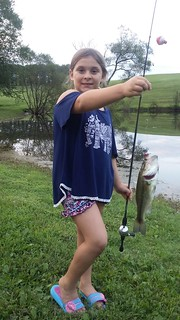 Stella Amoriello with her first catch, a largemouth bass.