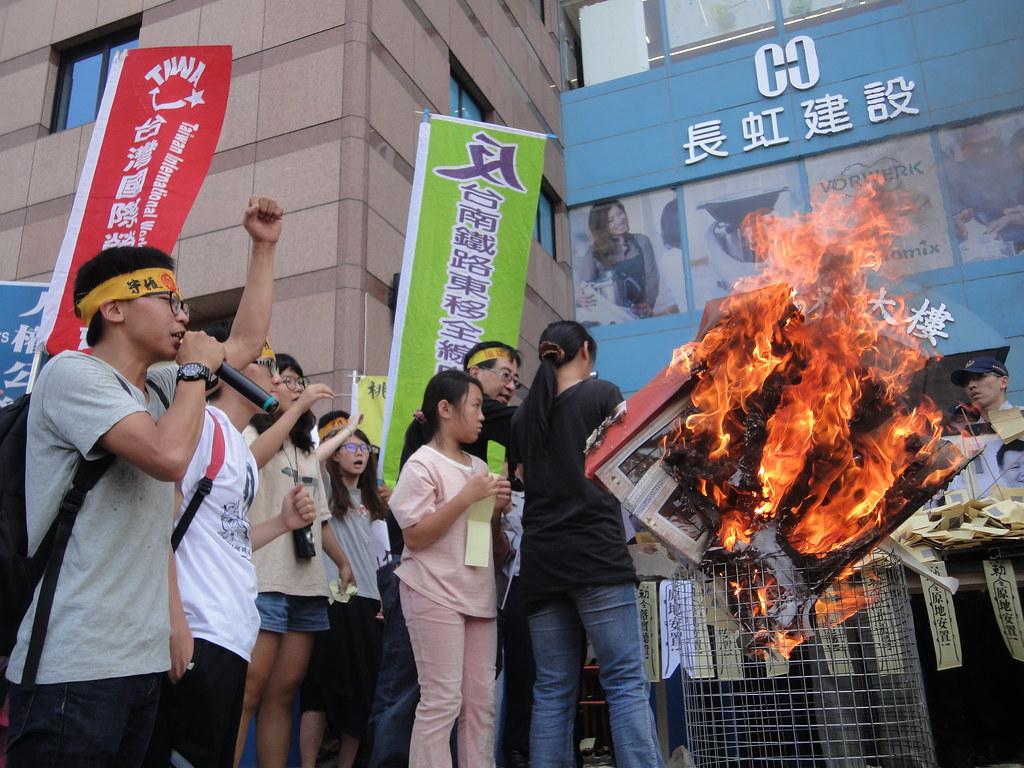 反迫遷團體在民進黨部前燃燒象徵居民家園的房屋,抗議政府迫遷人民。(攝影:張智琦)