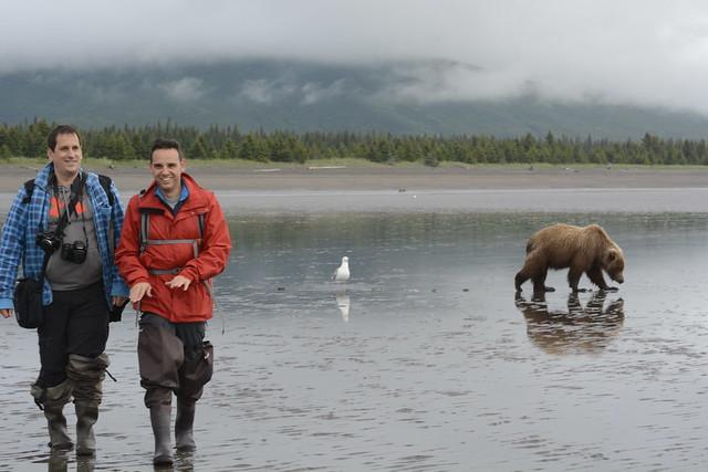 Sele e Isaac con un oso detrás en una playa de Lake Clark (Alaska)