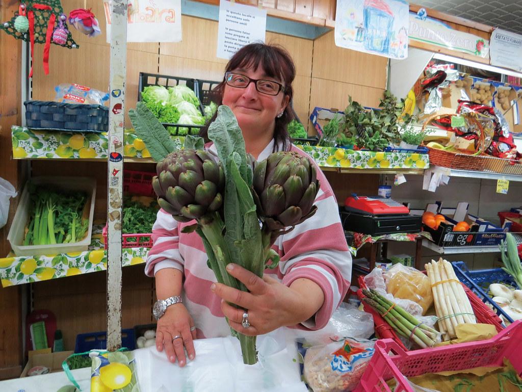 艾琳娜靦腆地拿起自家種植的朝鮮薊接受拍照。