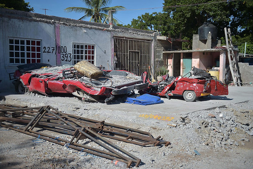 Red cars are crushed flat in the front yard of a home.