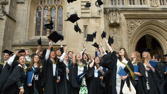 A group of graduates throwing their mortar boards up outside Bath Abbey