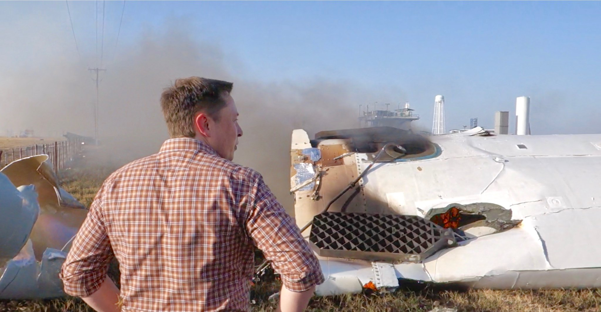 Elon Musk overlooking the remains of F9R | by jurvetson