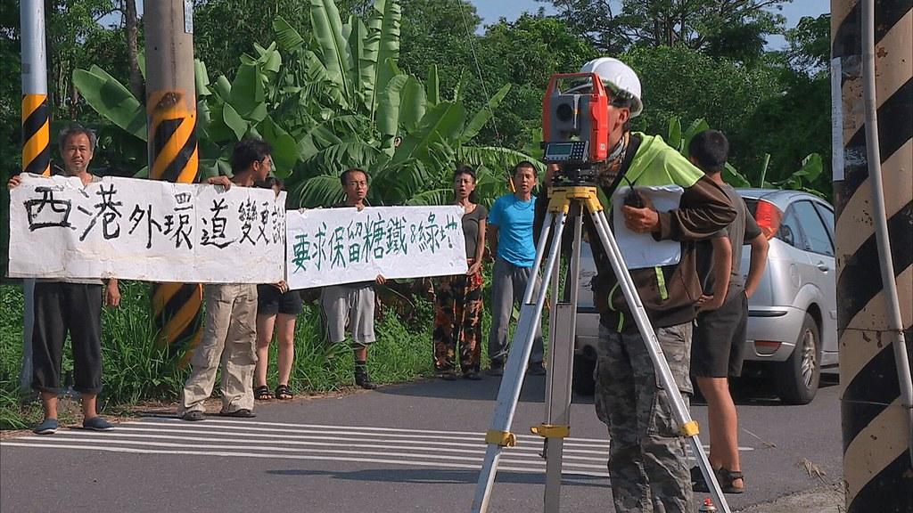 925-2-3 反西港外環道不當開闢自救會在西港旗站前一字排開,對著正在進行道路測量的工作人員喊話。