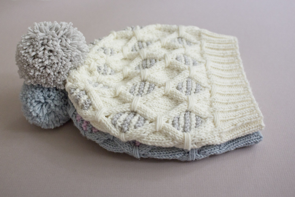 A pile of two knitted hats in grey and white