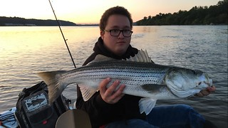 Lou Walden holds up a really nice striped bass