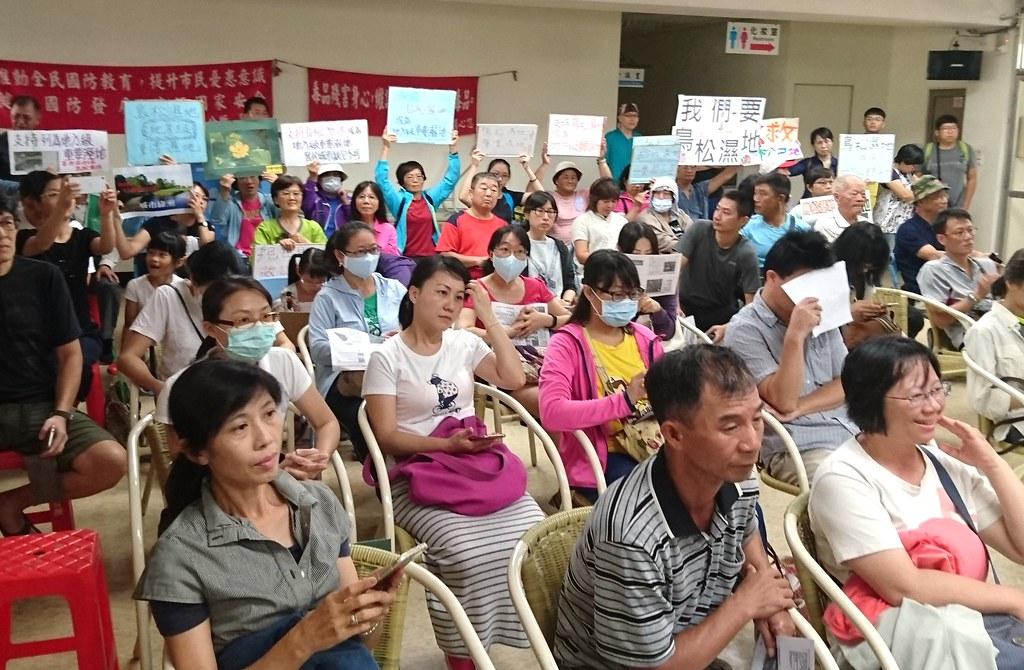 民眾在會場舉牌表達支持鳥松濕地維持地方級重要濕地。攝影:李育琴。