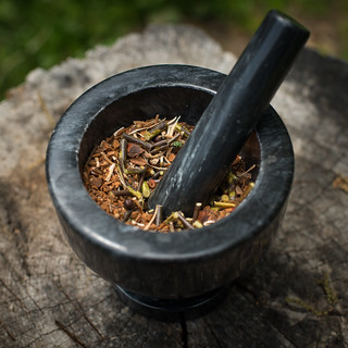 Twigs and Spices in Mortar w/ Pestle on a Wooden Stump | by goingslowly