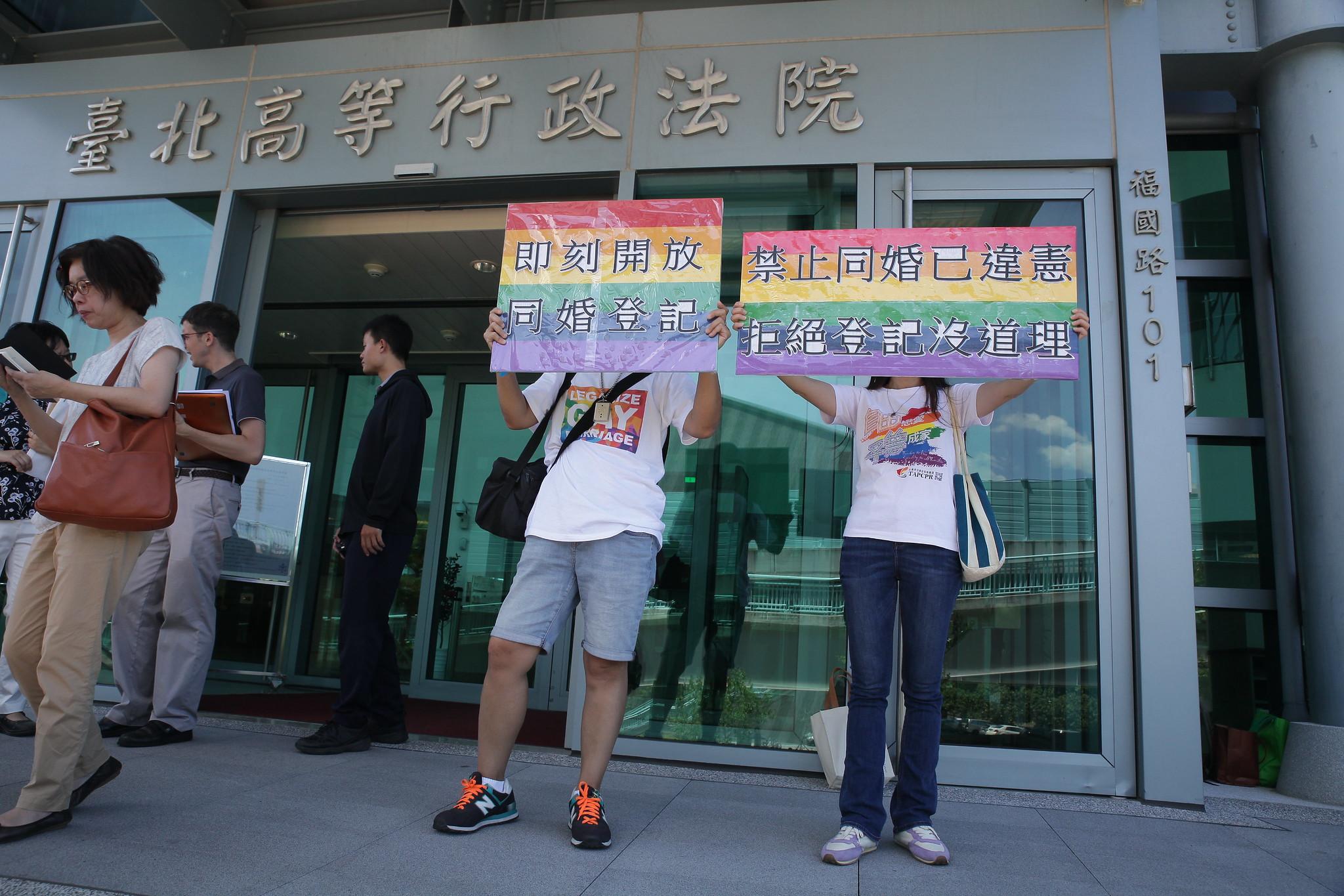 支持同婚的民眾8月9日前在法院前舉牌。(攝影:陳逸婷)