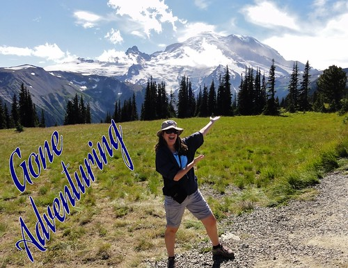 Image shows me at Mount Rainier National Park, gesturing to the mountain from across a meadow. The words Gone Adventuring are in blue beside me.
