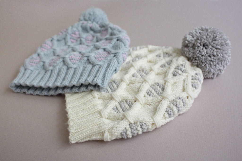 Two knitted hats, each with a pom pom and patterned with diamond shaped cables.