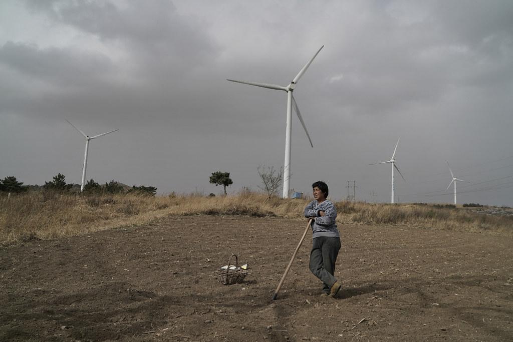 天陰沈沈的,風很大,阜新塔山頂上那幾座新建的風電塔轉得呼呼響。陳芳在等風後的那場大雨,以便播種。其實,在遼西大地,「等風」的又何止是農民陳芳。阜新,這座中國最早建立起來的能源基地之一,2001年被國務院正式認定為全中國第一個資源枯竭型城市,她的轉型之路艱難且漫長。攝影:Stam Lee