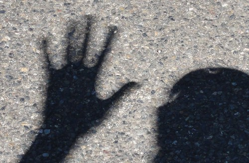 Image shows a shadow of my spread hand and a bit of my head projected onto pavement. Instead of being dark black with sharp edges, my shadow is gray, with very fuzzy edges.