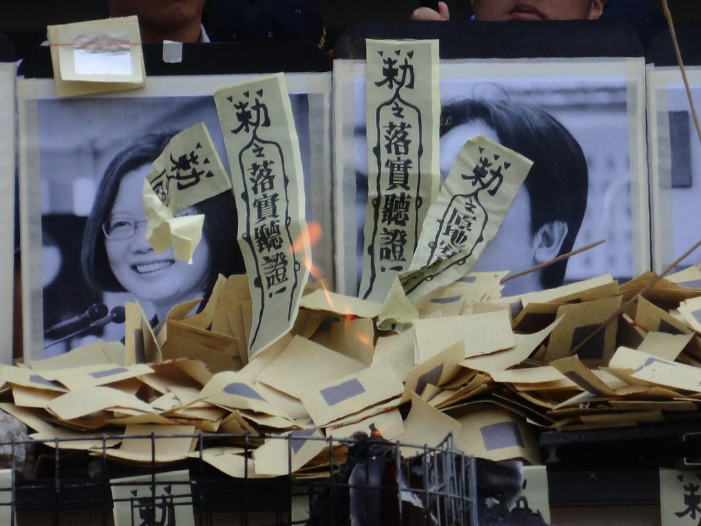 抗爭者在迫遷惡鬼的照片前焚燒冥紙。(攝影:張智琦)