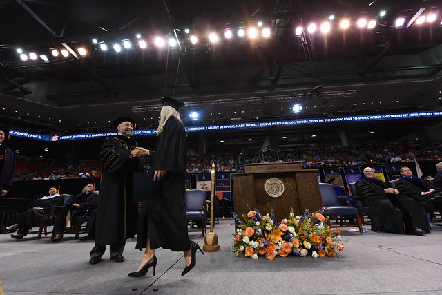Auburn President Dr. Leath shakes hands with a graduate on stage.