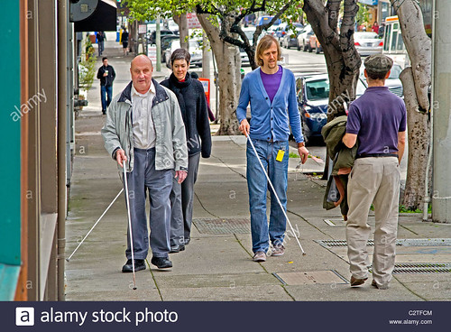 accompanied-by-an-instructor-a-blind-man-using-a-white-cane-teaches-C2TFCM | by vp100194