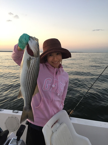 Bing Wilson happily holds up a nice striped bass she caught