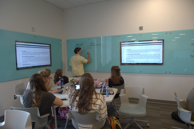 A student is writing on a blue glass board near a TV monitor as a group of students at the desk behind him watch.