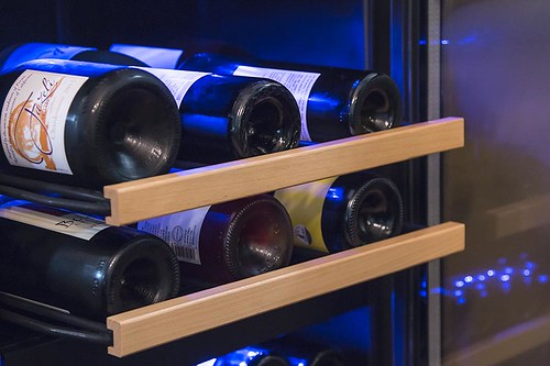 wine bottles on racks in a wine cooler / refrigerator | by yourbestdigs