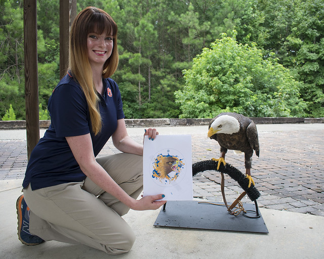 Robyn Miller kneels next to spirit while showing a lure design.