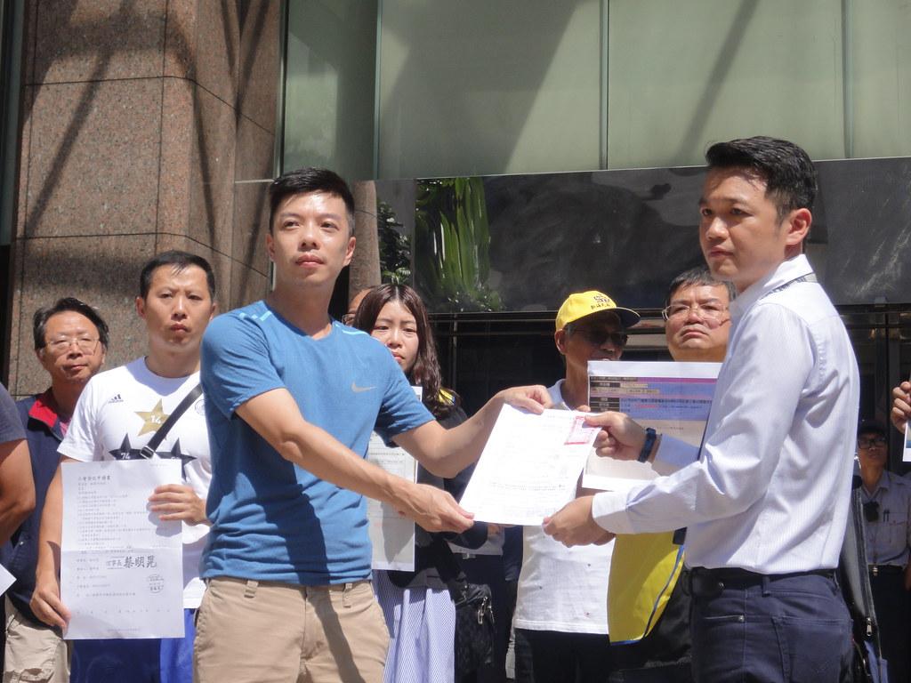 勞動部勞動關係司科長許根魁(右)接下不當勞動行為裁決申請書。(攝影:張智琦)