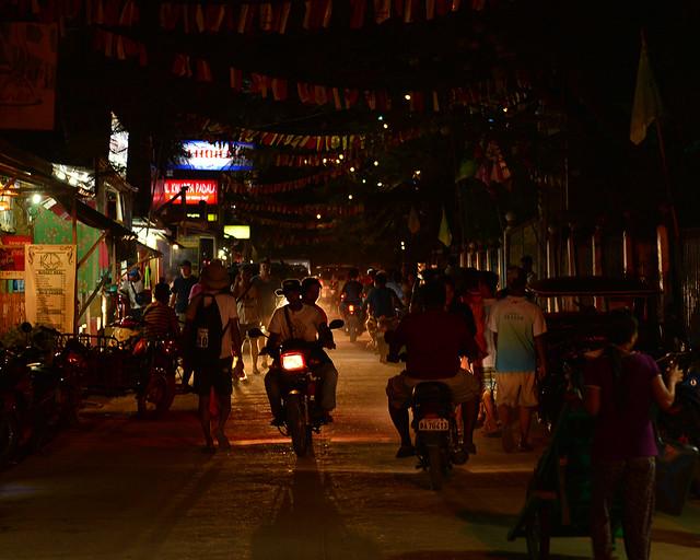 Escenario típico de Filipinas en la noche con motos y establecimientos encendidos