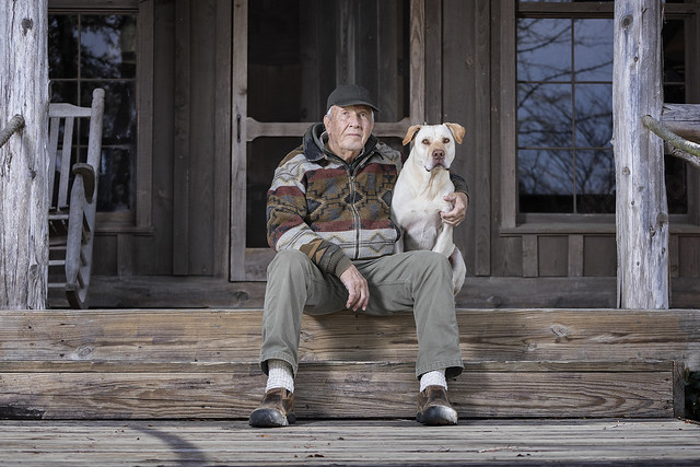 Pat Dye sits on the porch with his dog.