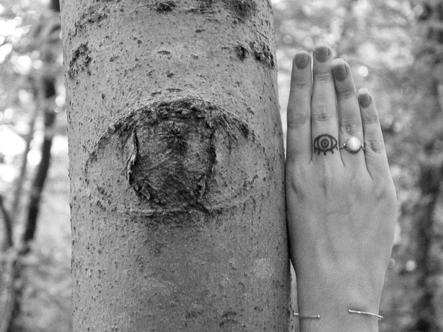 eye shape in tree bark next to hand with eye tattoo