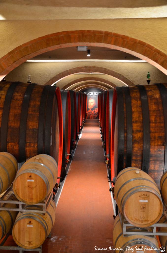 Ao fundo a foto da rótulo do Il Grigio o vinho tinto chianti Clássico da propriedade.