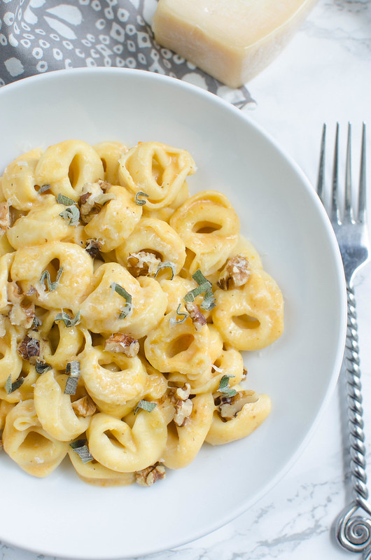 Pumpkin Alfredo Tortellini - a fall twist on the classic alfredo sauce recipe! Tossed with tortellini and sprinkled with fresh sage and walnuts. You won't be able to resist this one!