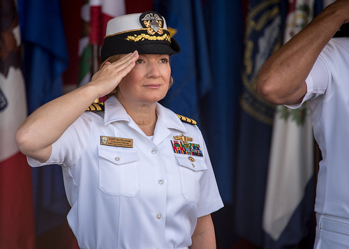 Capt. Jen Ellinger, the incoming commanding officer of the Ticonderoga-class guided-missile cruiser USS Lake Champlain (CG 57), salutes Rear Adm. John Fuller, commander, Carrier Strike Group 1, during a change of command ceremony on the ship.